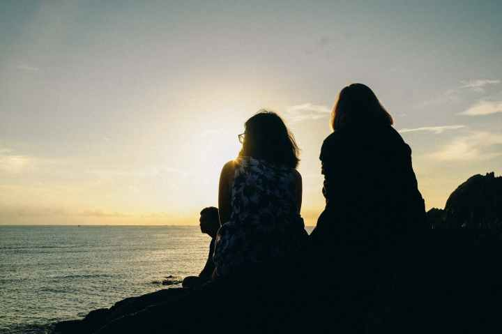 silhouette of two women facing body of water